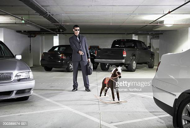 young businessman aiming car alarm remote control at rocking horse - car alarm stock photos and pictures