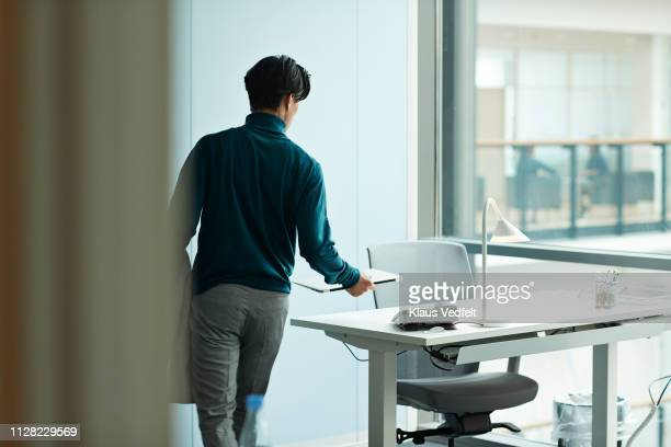 young businessman airing at desk in open office - hot desking stock pictures, royalty-free photos & images