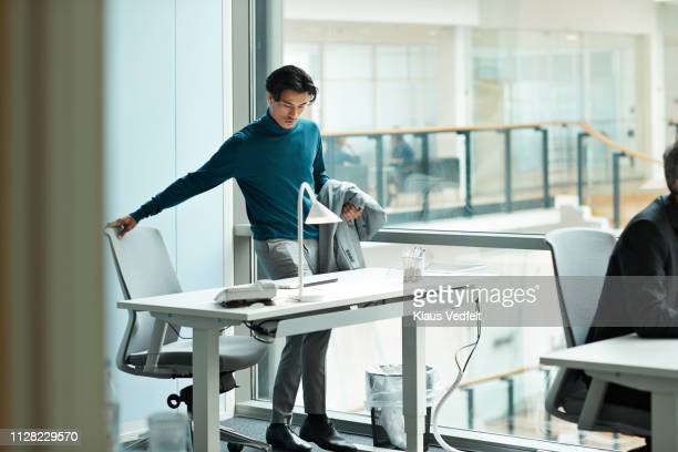 young businessman airing at desk in open office - arrival stock pictures, royalty-free photos & images