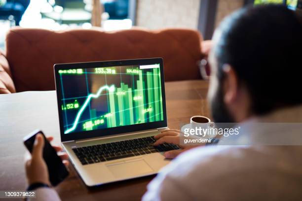 young businessman analyizing financial charts - looking over shoulder stock pictures, royalty-free photos & images