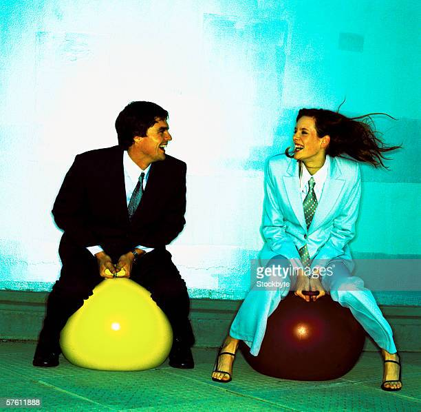 Young businessman and a young businesswoman sitting on space hoppers (toned)