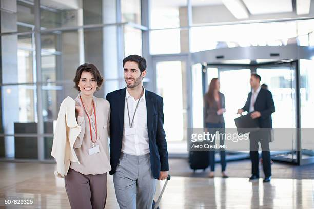 Young businessman and businesswoman arriving at conference centre