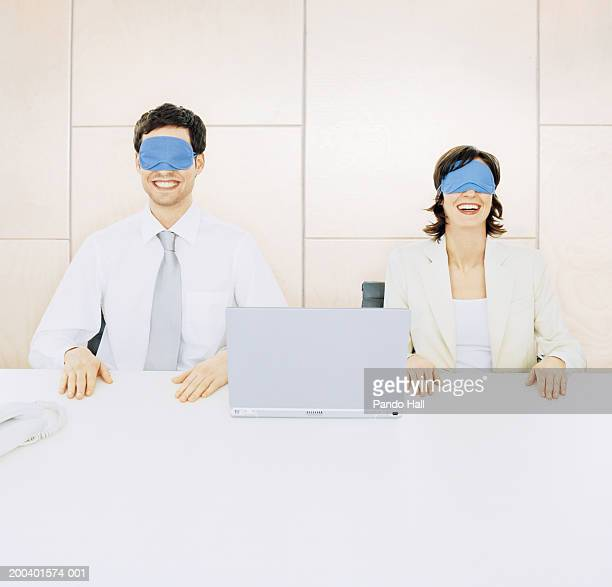 Young businessman and businesswoman by laptop, masks over eyes
