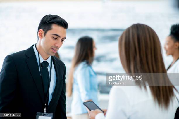 a young businessman and businesswoman exchange contact information at a conference - fatcamera stock pictures, royalty-free photos & images
