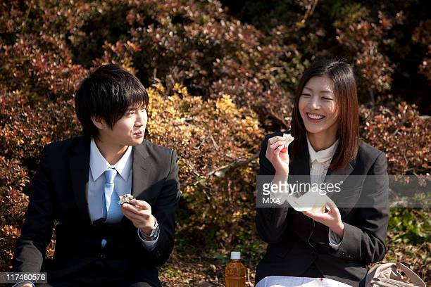 Young businessman and businesswoman having lunch at park