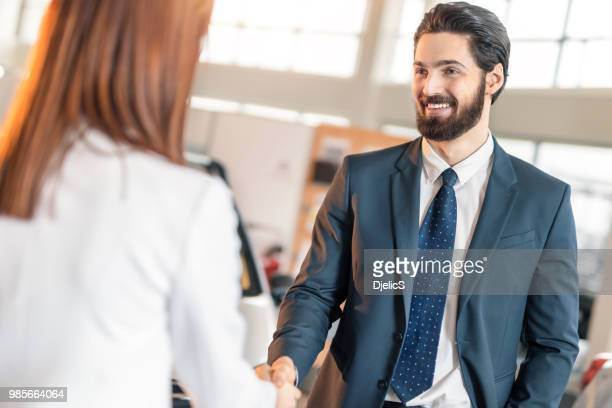 young businessman and businesswoman shaking hands in car dealership. - tradeshow stock pictures, royalty-free photos & images