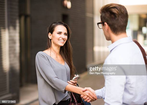 Young businessman and businesswoman shaking hands outside office, London, UK