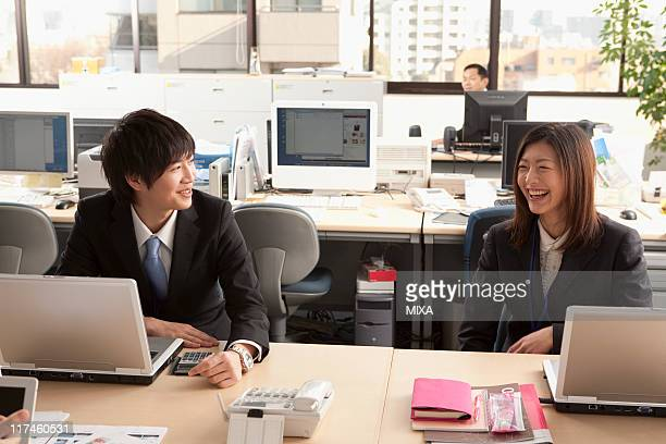 Young businessman and businesswoman talking at office