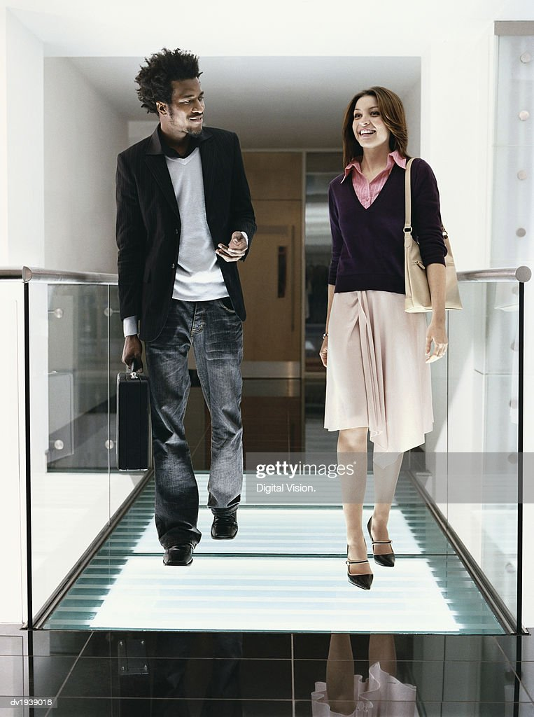 Young Businessman and Businesswoman Walk Down a Corridor in an Office, Talking and Smiling : Stock Photo
