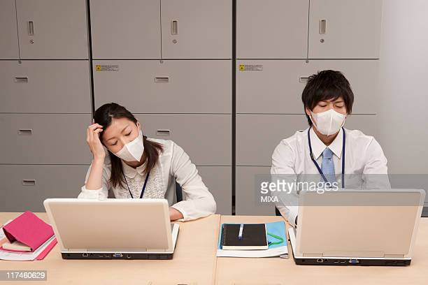 Young businessman and businesswoman working and wearing mask