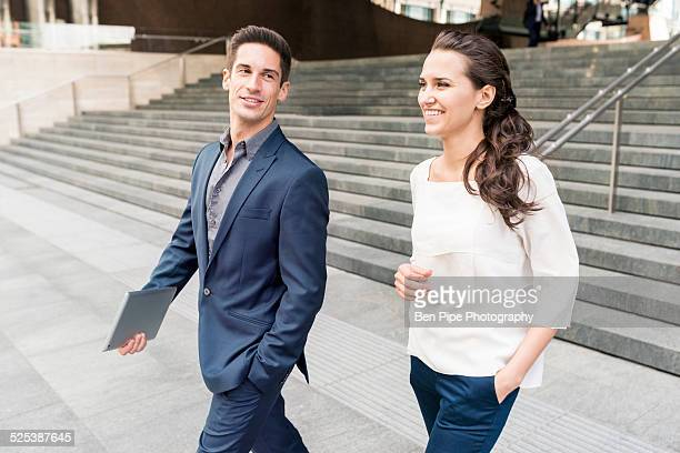 Young businessman and woman chatting whilst walking, London, UK