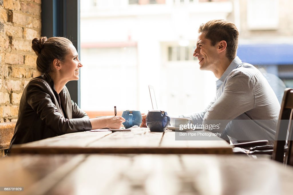 Young businessman and woman meeting in cafe : Stock Photo