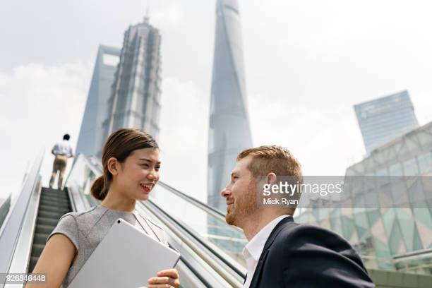 Young businessman and woman moving up escalator in Shanghai financial centre, Shanghai, China