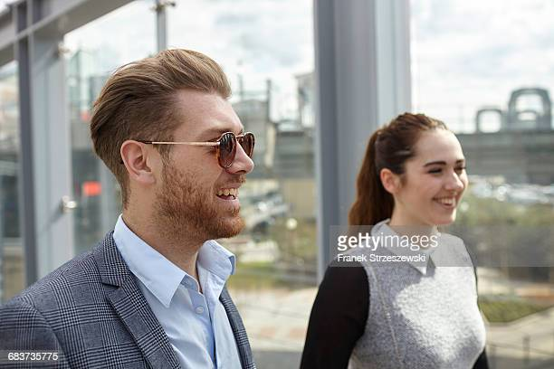Young businessman and woman on city footbridge, London, UK