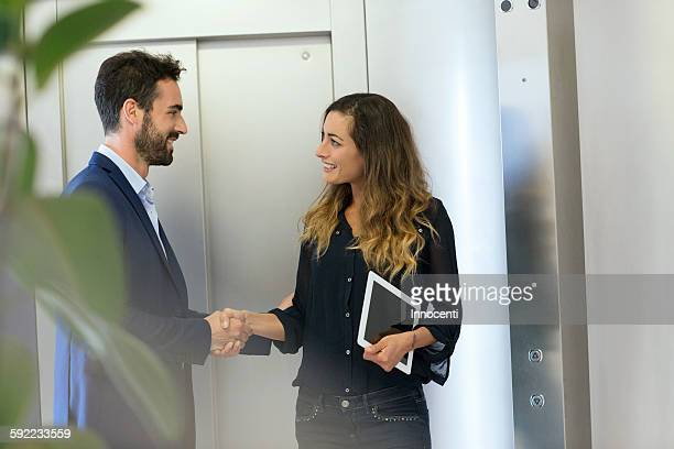 Young businessman and woman shaking hands at elevator