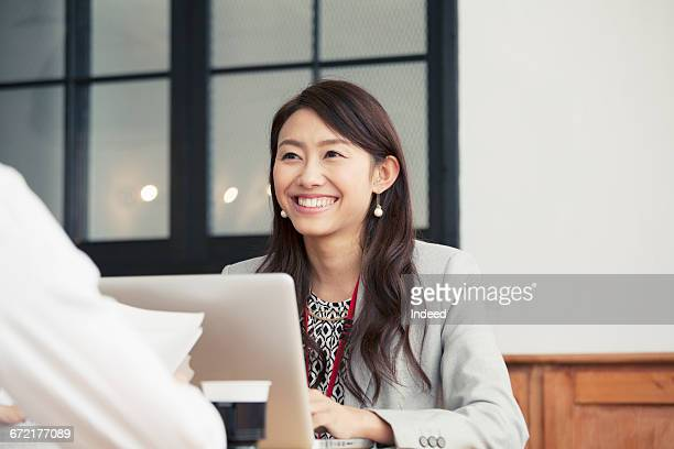 young businessman and woman talking at desk - japanese ol ストックフォトと画像