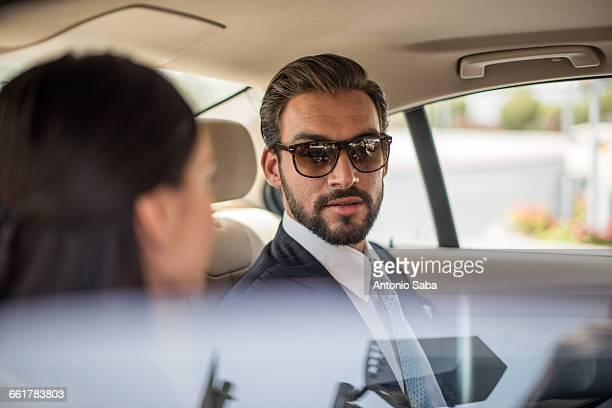 young businessman and woman talking in car backseat, dubai, united arab emirates - gulf countries stock pictures, royalty-free photos & images
