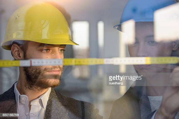 Young businessman and woman wearing hard hats measuring window in new office