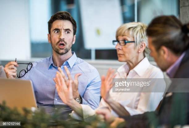 young businessman arguing with his colleague on a meeting in the office. - anger stock pictures, royalty-free photos & images