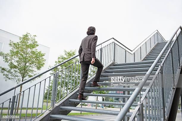 Young businessman ascent ladder of success job