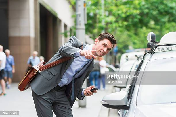 Young businessman asking address to Taxi driver