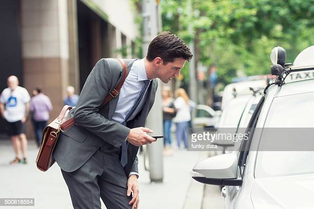 Young businessman asking an address to the taxi
