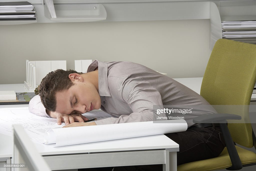 Young businessman asleep on desk : Stock Photo