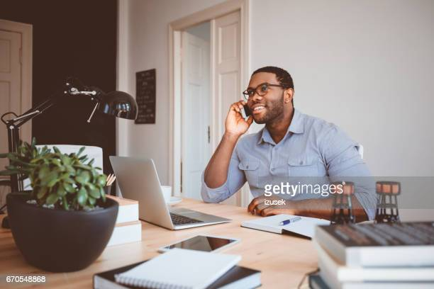 young businessman at home office talking on phone - remote work stock pictures, royalty-free photos & images