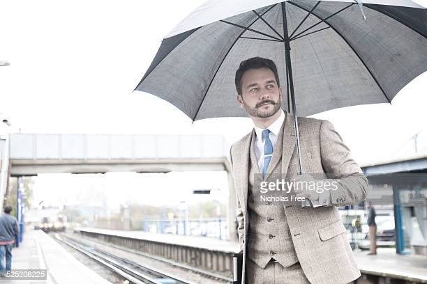 Young Businessman at the Train Station Carrying an Umbrella