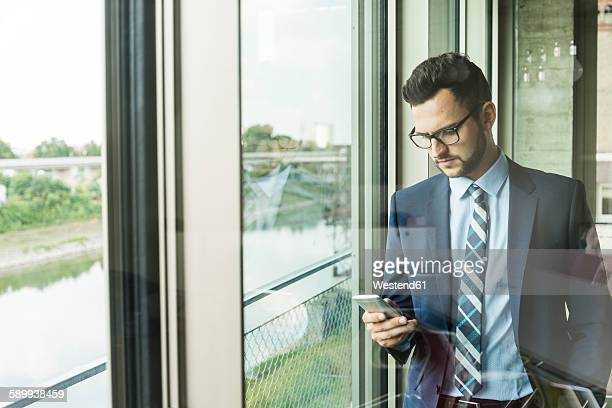 Young businessman at the window looking on cell phone