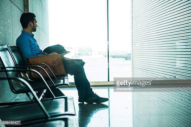 Young businessman at waiting area looking out of window