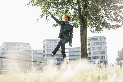 Young businessman balancing on slackline - gettyimageskorea