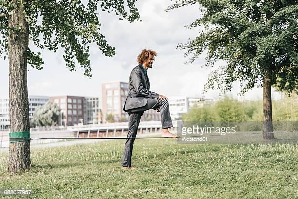 Young businessman balancing on slackline