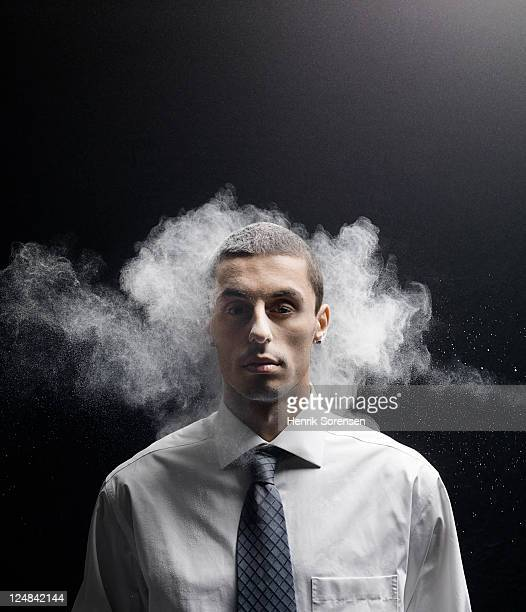 young businessman being hit by white powder
