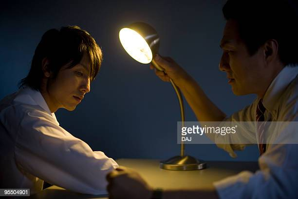 Young Businessman Being Questioned In Interrogation Room