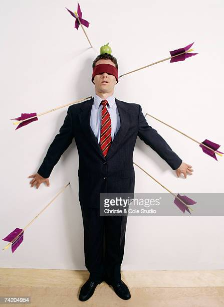Young businessman, blindfolded, standing against wall with apple on head, surrounded by arrows