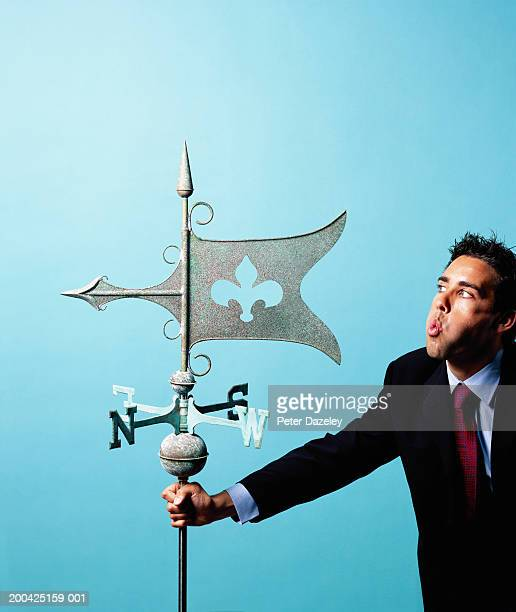 Young businessman blowing wind vane