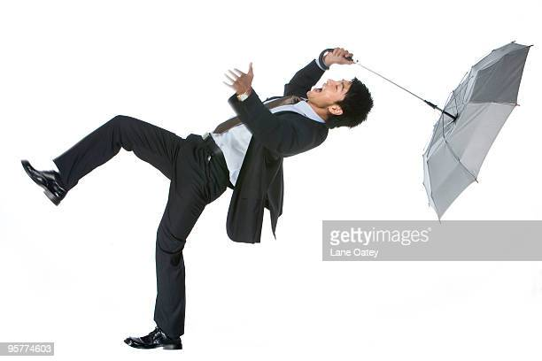 Young businessman blown away in the wind