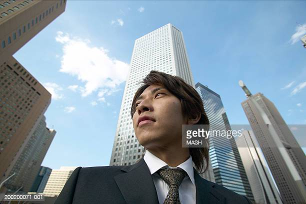 Young businessman by skyscrapers, low angle view