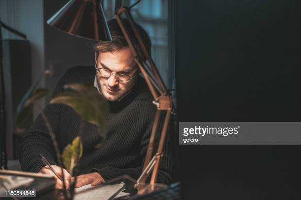 young businessman calculating in the office at night - angle poise lamp stock pictures, royalty-free photos & images