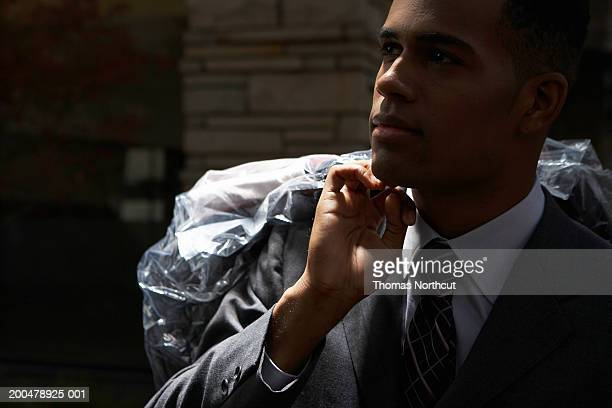 young businessman carrying dry cleaning bag over shoulder, night - dry cleaned stock pictures, royalty-free photos & images