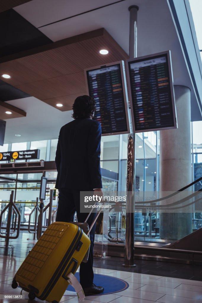 Junger Geschäftsmann Überprüfung Flugzeit am Flughafen Abfahrtstafel : Stock-Foto