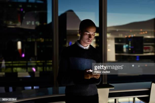 young businessman checking phone inside office at nighttime - portability stock pictures, royalty-free photos & images