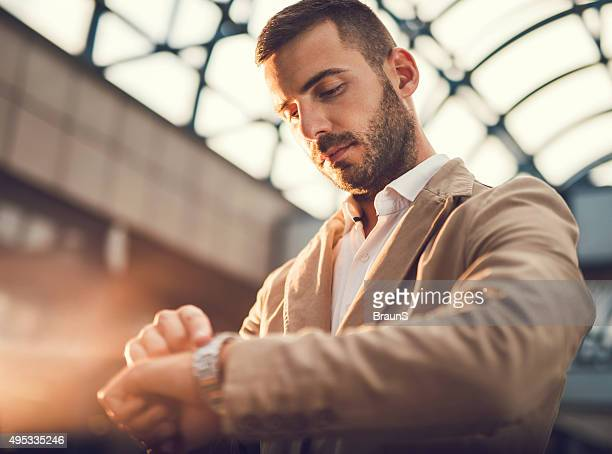 young businessman checking the time on his wristwatch. - tijdmeter stockfoto's en -beelden