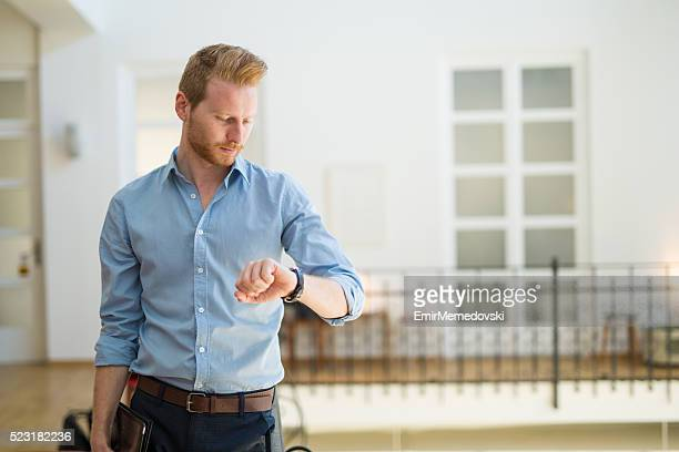 Young businessman checking the time on his wristwatch.