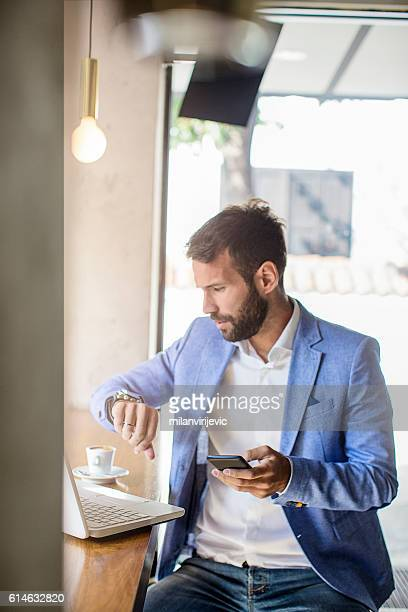 Young businessman checking the time