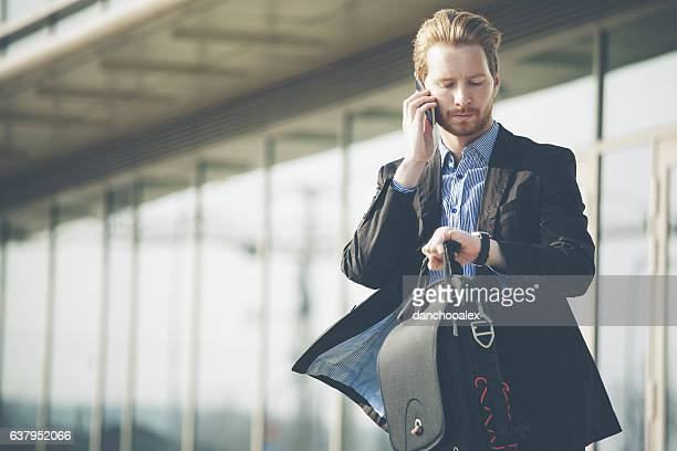 young businessman checking time and talking on the cell phone - beat the clock stock photos and pictures