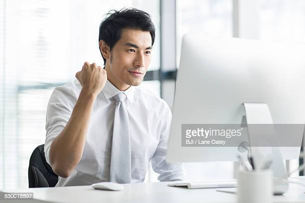 Young businessman cheering in office
