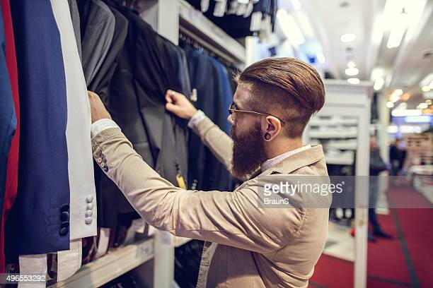 Young businessman choosing suits in a clothing store.