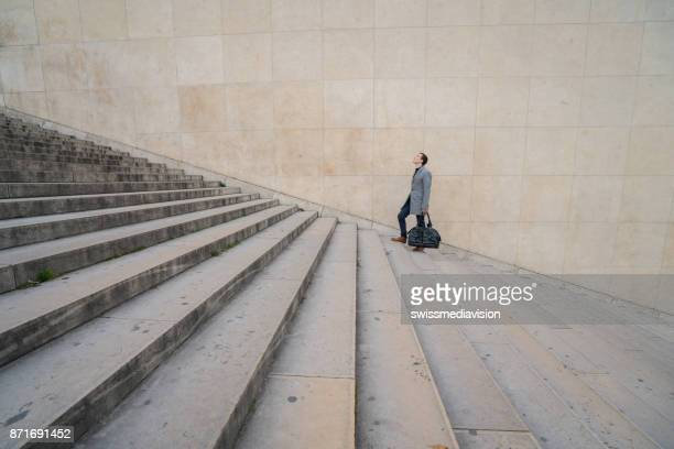 Young businessman climbing stairs up, Paris